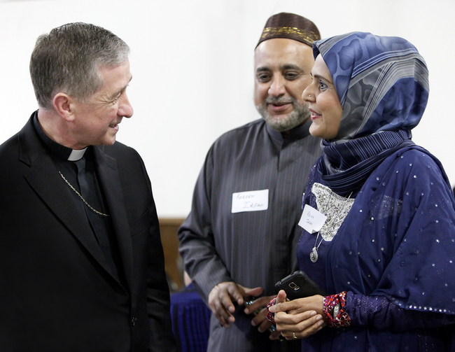 "Chicago Archbishop Blase J. Cupich visits with Kareem and Rana Irfan before the19th annual Catholic-Muslim ""iftar"" dinner at the Zakat Foundation of America in Bridgeview, Ill (CNS photo/Karen Callaway/Catholic New World)."