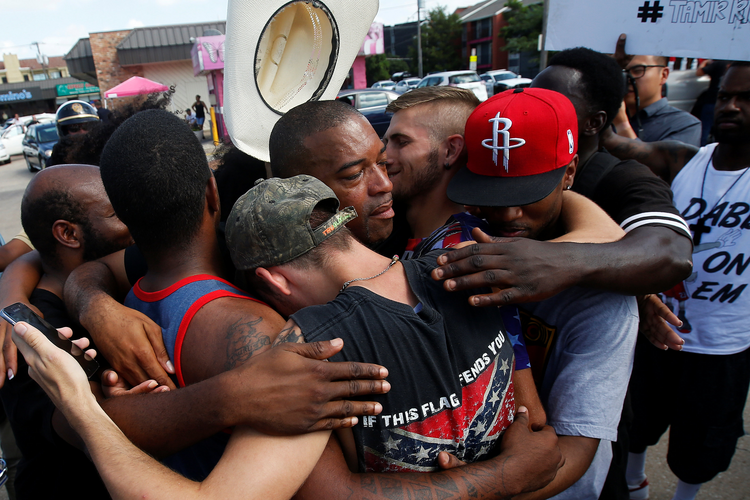 People hug after taking part in a prayer circle July 10 following a Black Lives Matter protest in the wake of multiple police shootings in Dallas (CNS photo/Carlo Allegri, Reuters).