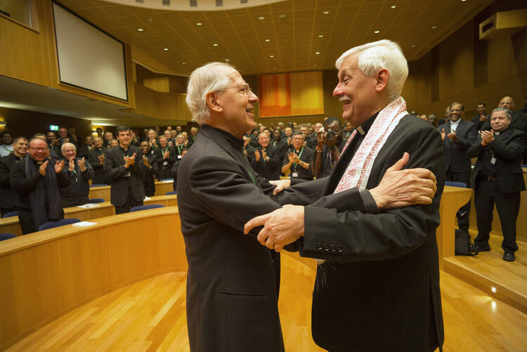 Jesuit Father Arturo Sosa, right, the new superior general of the Society of Jesus, greets the previous superior general, Jesuit Father Adolfo Nicolas, after his election in Rome Oct. 14  (CNS photo/Don Doll, S.J.).