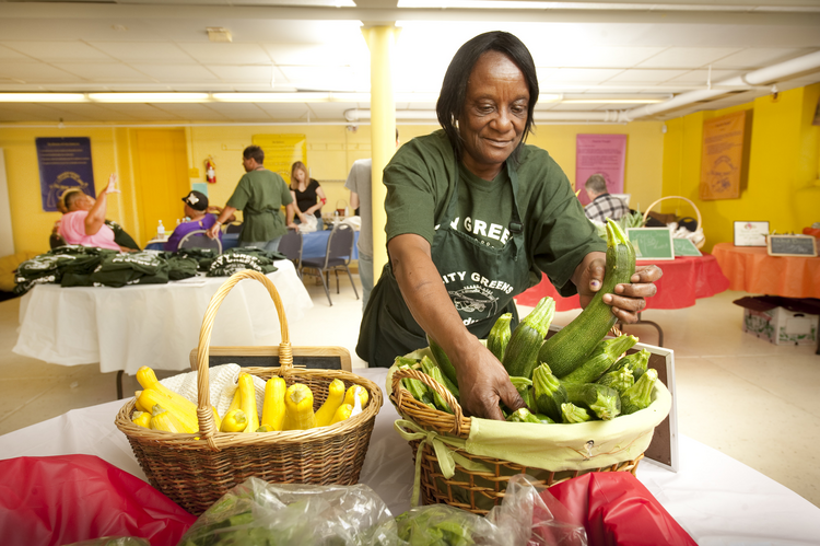 Betty Howard arranges produce at the City Greens at Midtown Center in St. Louis, June 17, 2010. The project is sponsored by Catholic Charities (CNS photo/Lisa Johnston, St. Louis Review).