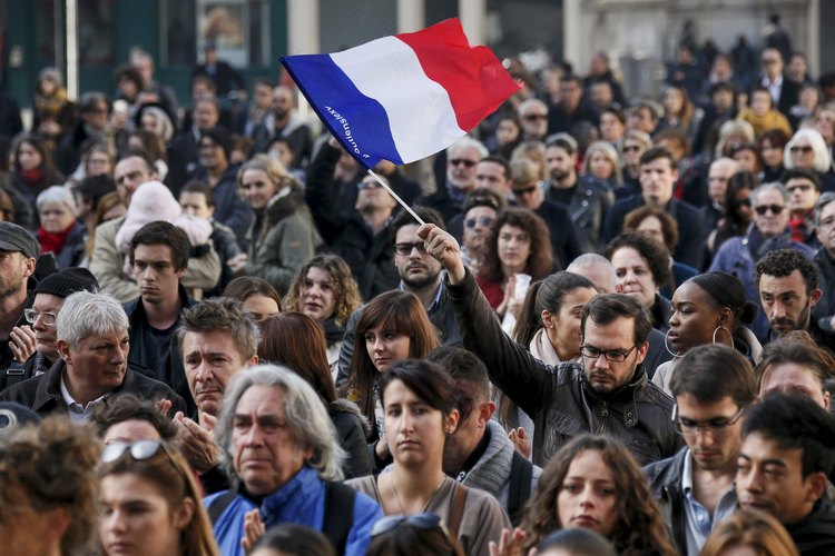 A man waves a French flag as several hundred people gather to observe a minute of silence in Lyon, France, Nov. 16 (CNS photo/Robert Pratta).