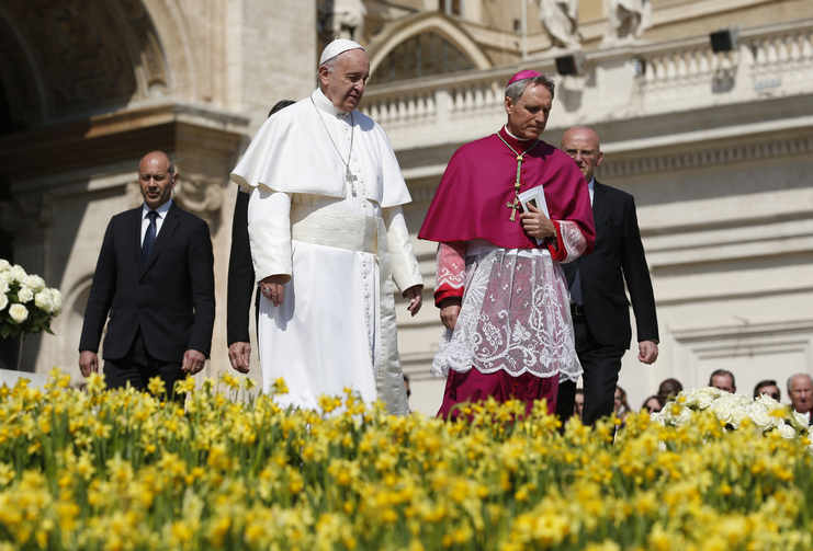 Pope Francis walks past flowers as he prepares to greet the crowd at the conclusion of Easter Mass in St. Peter's Square at the Vatican March 27. Also pictured is Archbishop Georg Ganswein, prefect of the papal household (CNS photo/Paul Haring).