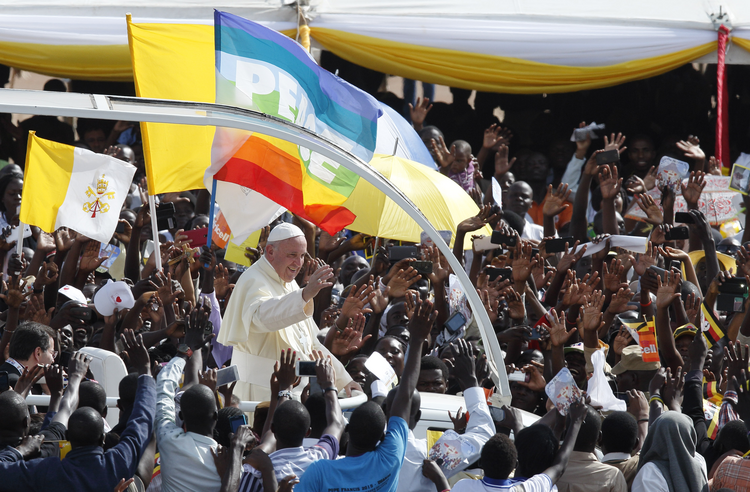 The Vatican flag and a peace banner are seen as Pope Francis greets the crowd as he arrives for a meeting with young people at the Kololo airstrip in Kampala, Uganda, Nov. 28 (CNS photo/Paul Haring).