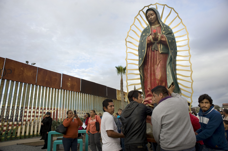 A statue of Our Lady of Guadalupe is unloaded from a truck after a Nov. 19 procession to the U.S.-Mexico border fence in Tijuana, Mexico, where Mass was celebrated (CNS photo/David Maung).