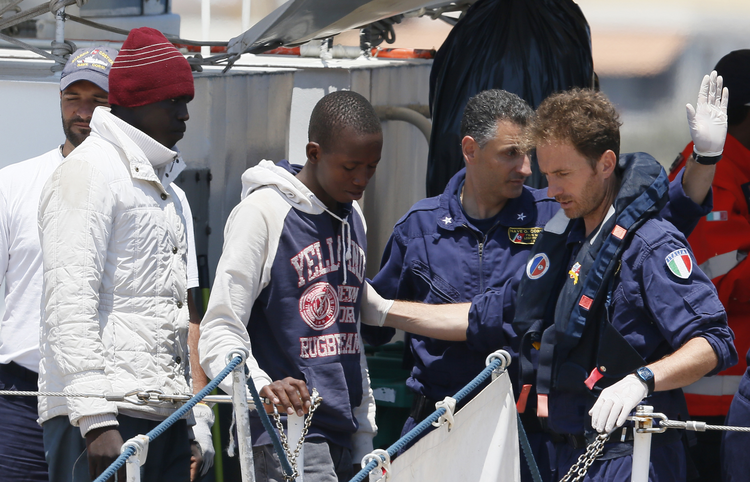 Italian coast guards instruct immigrants as they disembark from a coast guard ship at port in Lampedusa, Italy