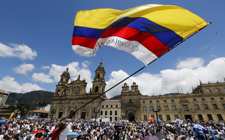 "A man waves a national flag during the ""March For Life"" March 8 in Bogota, Colombia. The event supported peace negotiations between the government and the Revolutionary Armed Forces of Colombia. (CNS photo/John Vizcaino, Reuters)"