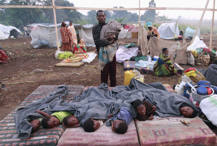 Congolese children displaced by fighting rest in open at camp in Uganda, July 13.