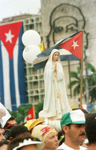 A statue of Mary is held above the crowd attending an outdoor Mass with Pope John Paul II during his 1998 visit to Cuba.