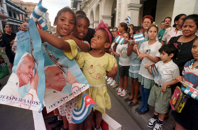 Children holding Cuban flags and images of Pope John Paul II line a Havana street Jan. 20 staking out positions where they might get a glance of the pontiff on his arrival to Cuba Jan. 21, 1998. (CNS photo/Alyssa Banta)