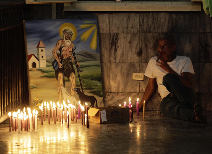 A worshipper smokes a cigar beside a painting in the shrine of St. Lazarus in the town of El Rincon, Cuba, in December 2013. (CNS photo/Desmond Boylan, Reuters)