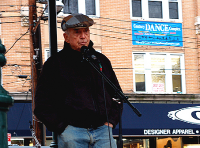 A Familiar Pose. Father Berrigan speaks in October 2006 at the 3rd Annual Staten Island Freedom & Peace Festival. Photo by Clara Sherley-Appel; Wikicommons