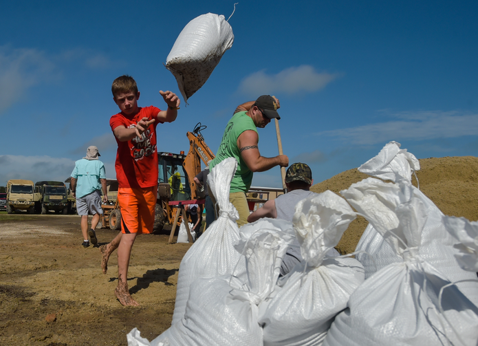 Dylan Heinan, among other volunteers, piles sandbags in an effort to stop flood waters from rising in Lake Arthur, La., Wednesday, Aug. 17, 2016. (Scott Clause/The Daily Advertiser via AP)