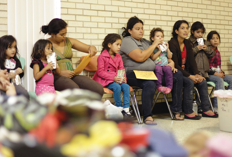 THE HEART OF TEXAS. Migrants sit at the Sacred Heart Catholic Church temporary shelter in McAllen, Tex.