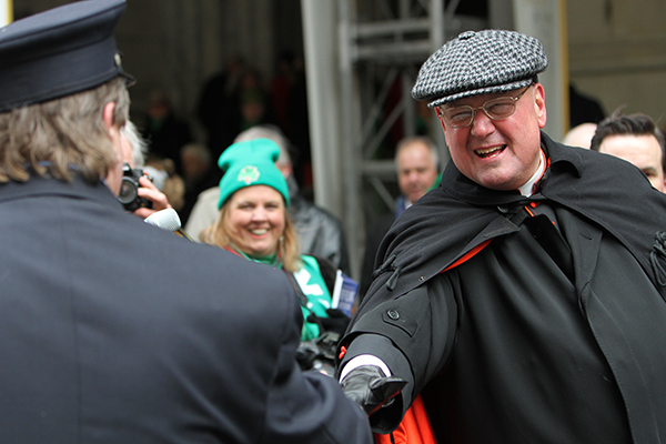 Cardinal Timothy M. Dolan of New York greets a New York City firefighter while reviewing the 253rd annual St. Patrick's Day parade in front of St. Patrick's Cathedral in New York on March 17, 2014. RNS photo by Gregory A. Shemitz