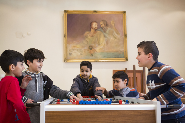 Boys plays foosball March 25 at Don Bosco youth center in Istanbul. (CNS photo/Elie Gardner)