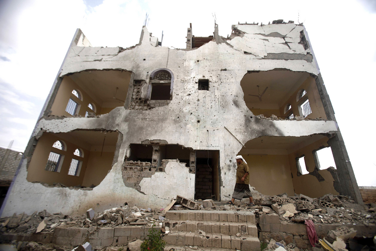 Tribesman walks near a building damaged last year by U.S. drone airstrike in Yemen.