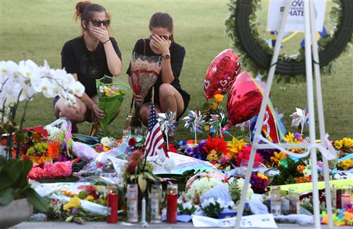 Kelli Cantu 24, left and Soe Aponte, 23, of Orlando become emotional Tuesday, June 14, 2016, as they visit a growing memorial at the The Dr. Phillips Center for the victims of the mass shooting at the Pulse Nightclub. (Red Huber/Orlando Sentinel via AP)