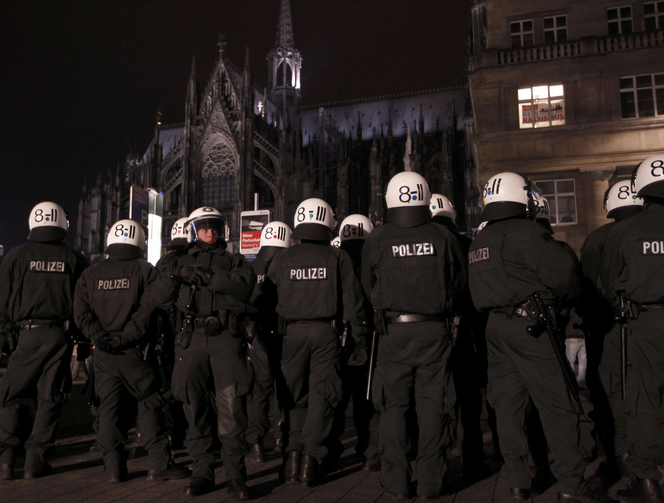 An anti-racism poster is displayed in a window of a building Jan. 21 as police stand guard in front of the cathedral in Cologne, Germany. (CNS photo/Ina Fassbender, Reuters)