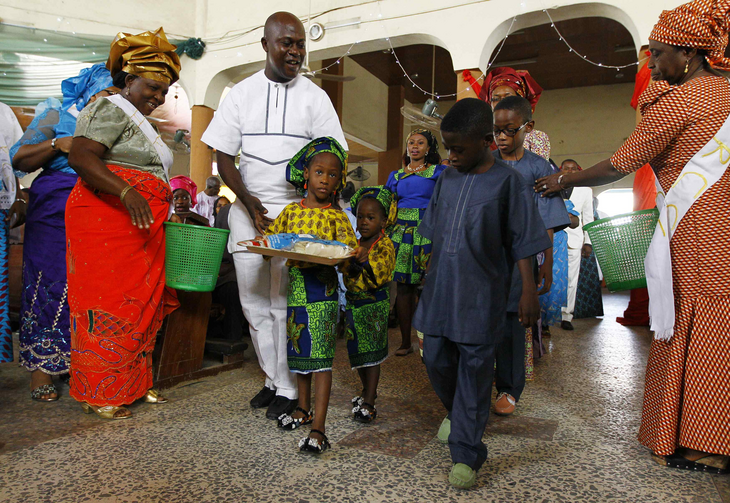 A family walks with gifts toward the altar during a New Year's Mass of thanksgiving at Holy Rosary Church in Abuja, Nigeria.