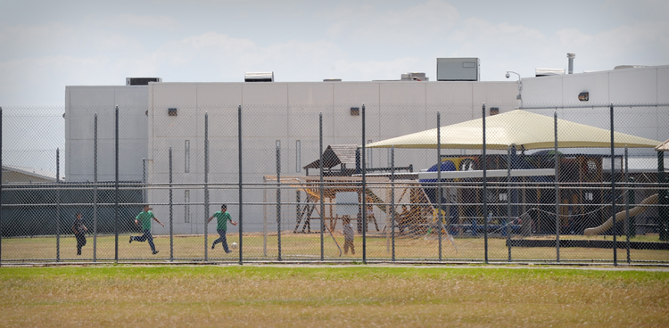 Children play in a double-fenced playground area outside the T. Don Hutto Family Residential Facility in Taylor, Texas. (CNS photo/Bahram Mark Sobhani)