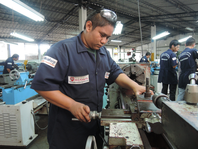 A metalworking student uses a lathe at a Fe y Alegria training center in San Salvador. The Jesuit educational organization uses training to improve the lives of young men and that might otherwise emigrate.