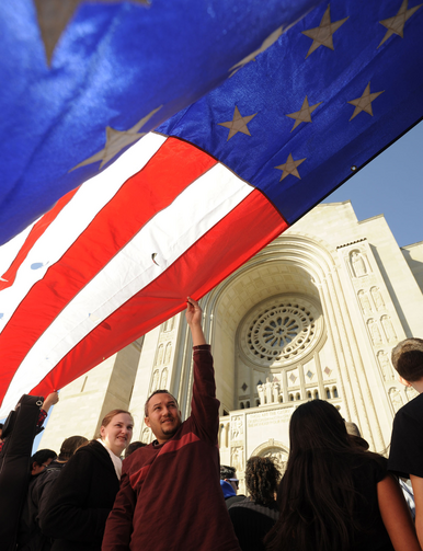 A man holds a large U.S. flag before an Oct. 14 Mass and Pilgrimage for Life and Liberty at the Basilica of the National Shrine of the Immaculate Conception in Washington. (CNS photo/Leslie E. Kossoff) (Oct. 15, 2012)