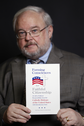 "John Carr, former executive director of the U.S. bishops' Department of Justice, Peace and Human Development, is pictured Feb. 28, 2012 holding ""Forming Consciences for Faithful Citizenship."""