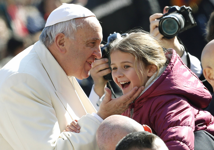 A child reacts after being kissed by Pope Francis as he arrives to lead the weekly audience in St. Peter's Square at the Vatican Feb. 18. (CNS photo/Giampiero Sposito, Reuters)