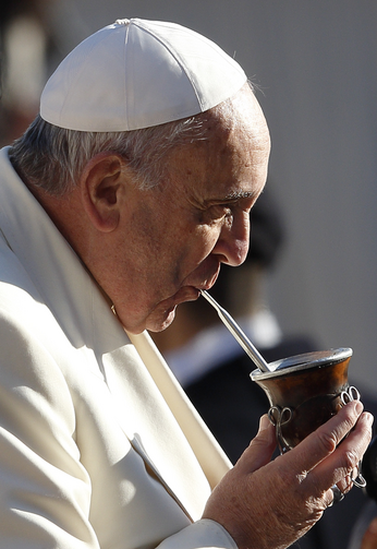Pope Francis drinks mate, the traditional Argentine herbal tea, presented by a Legionaries of Christ seminarian, as he arrives to lead his general audience in St. Peter's Square at the Vatican on Dec. 17. (CNS photo/Paul Haring)