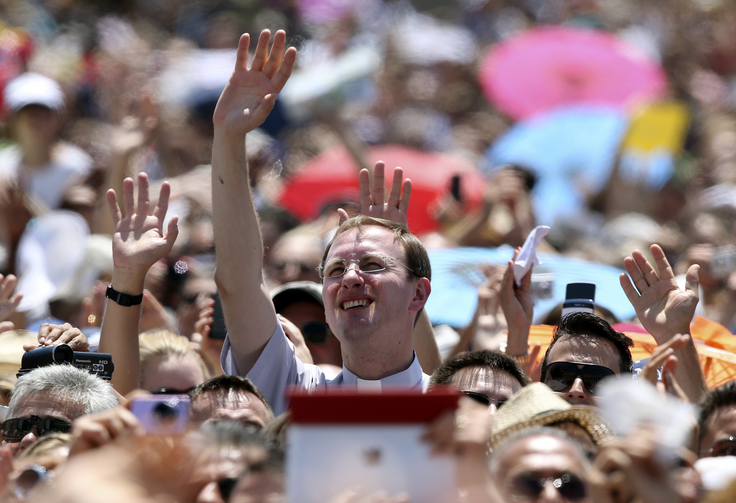 Clergyman waves as Pope Francis leads Angelus at Vatican.