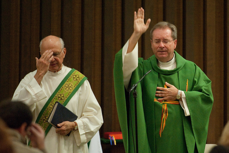 Father Gary Thomas, right, pastor of Sacred Heart Church in Saratoga, Calif., gives the final blessing during Mass Oct. 31., 2010