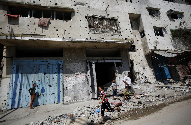 A Palestinian boy runs next to destroyed buildings in Gaza City Aug. 28. (CNS photo/Mohammed Saber, EPA)