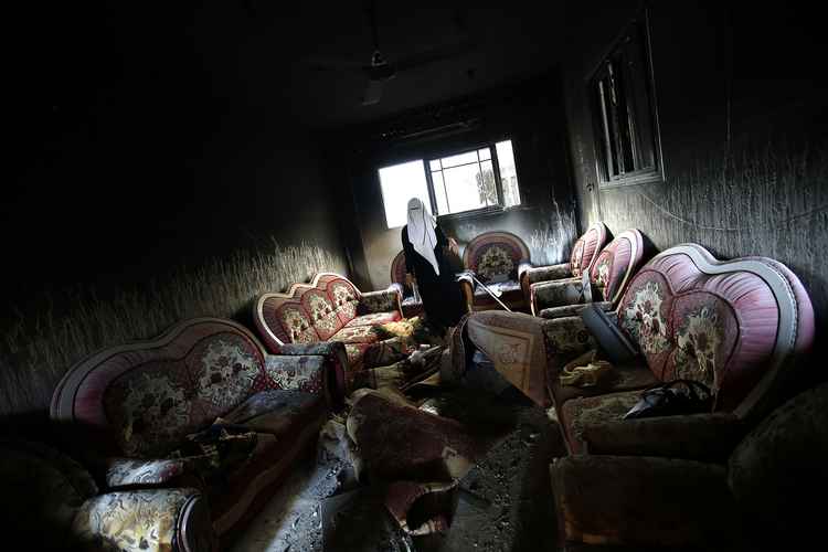 A Palestinian woman inspects a damaged house in Gaza City, Aug. 11.