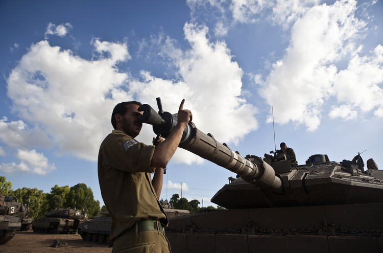 An Israeli soldier adjusts the barrel of a tank at a military staging area outside the northern Gaza Strip on July 14.