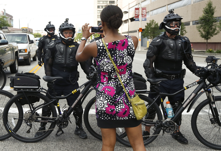 A demonstrator takes a picture of the police line during the Shut Down Trump & the RNC protest on July 17, in Cleveland. (AP Photo/John Minchillo)