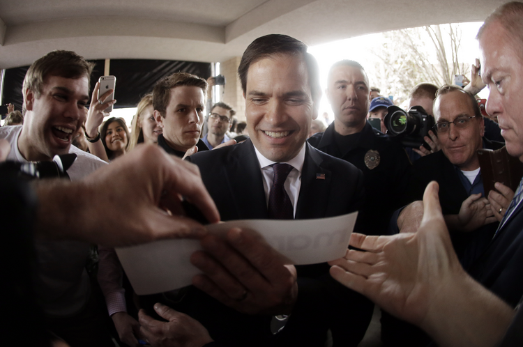 Republican presidential candidate Sen. Marco Rubio of Florida autographs a bumper sticker after speaking at a rally Sunday in Franklin, Tenn. (AP Photo/Mark Humphrey)