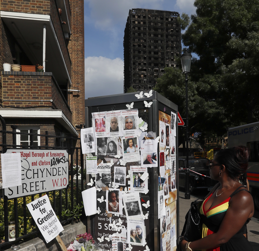A woman looks towards missing posters stuck on a phone box in front of the remains of Grenfell Tower in London on June 17, 2017. Police say it will take weeks or longer to recover and identify all the dead in the public housing block fire. (AP Photo/Kirsty Wigglesworth)
