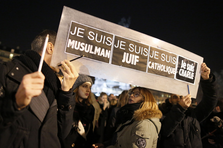 "People hold a placard that reads ""I am Muslim, I am Jewish, I am Catholic, I am Charlie"" during a Jan. 8 vigil in Paris, following the mass shooting at the offices of Charlie Hebdo, a satirical newspaper in Paris, Jan 8.."