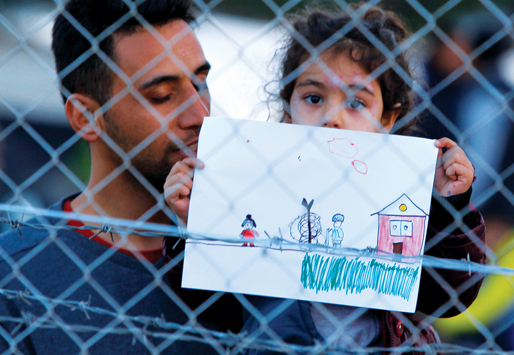 FENCED IN. A young refugee girl holds up a drawing in a makeshift camp on the Macedonian-Greek border, November 2015.