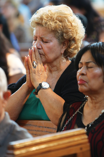 MAKING ALL WELCOME. A woman prays during a Spanish-language Mass at St. John-Visitation Church in the Bronx, N.Y., on Sept. 13.