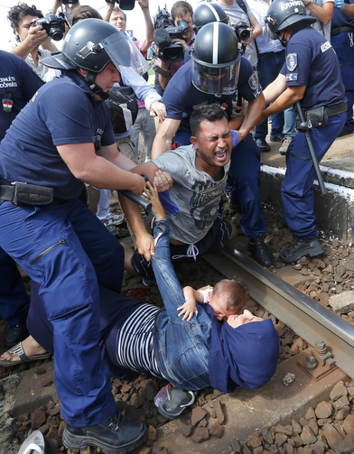 Hungarian policemen detain migrants on the tracks at a railway station in the town of Bicske, Hungary, Sept. 3. (CNS photo/Laszlo Balogh, Reuters)