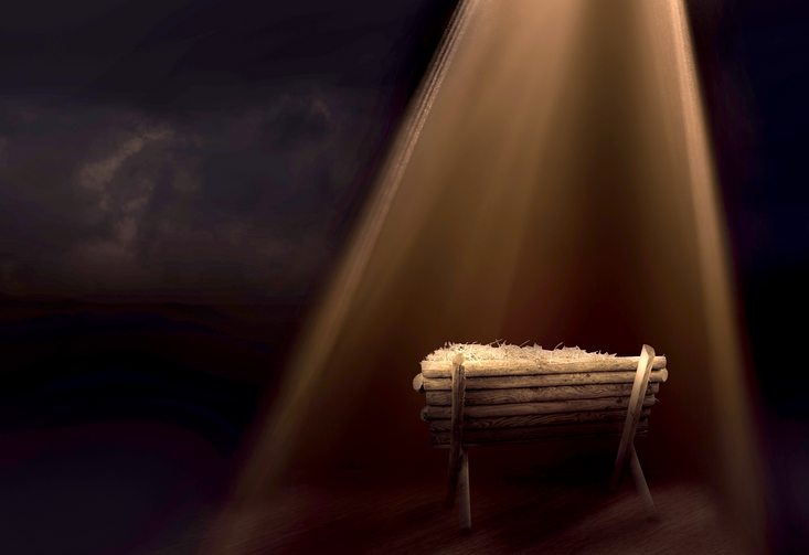 In a dark room, a wooden manger sits in a beam of light pouring through a window