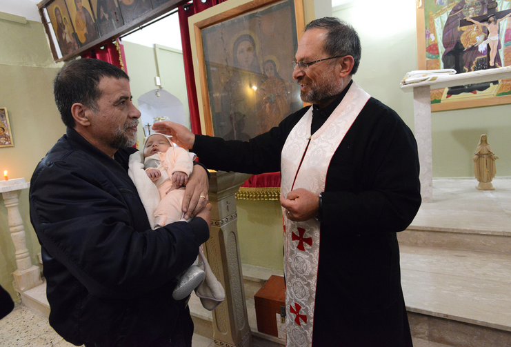Father Souhail Khoury blesses a baby after Easter Monday Mass at St. Mary's Church in Iqrit, Israel, April 13. The residents were expelled by the Israeli army in 1948 and have never been able to permanently return to the village. (CNS photo/Debbie Hill)