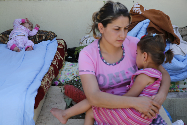 "A Christian woman who fled from the violence in Mosul, Iraq, holds her daughter as her baby sleeps June 27 at a shelter in Irbil, Iraq. Chaldean Catholic Patriarch Louis Sako of Baghdad said the city of Mosul ""is almost empty of Christians."""