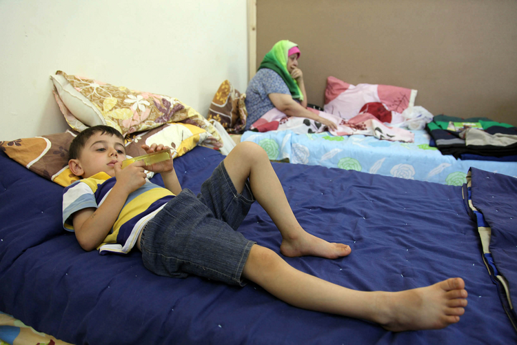 Iraqi Christian children who fled from religious-based violence in Mosul, Iraq, lie on a bed Aug. 21 at Mar Elias Monastery Church in Amman, Jordan. (CNS photo/Jamal Nasrallah, EPA)