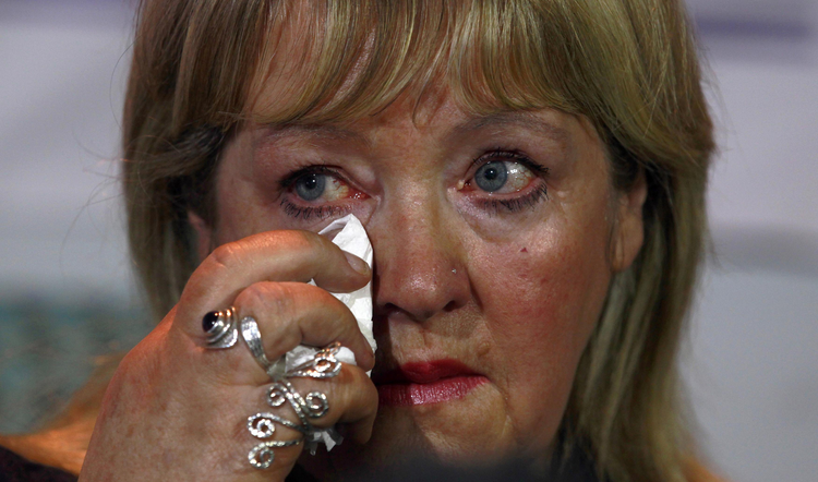 Woman who worked in a Magdalen laundries wipes tear during news conference in Dublin, Feb. 2013.