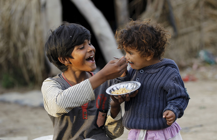 A boy feeds his sister in a slum on the outskirts of Islamabad March 30. The World Bank and global faith leaders are joining together to end extreme poverty around the world by 2030. (CNS photo/Caren Firouz, Reuters)