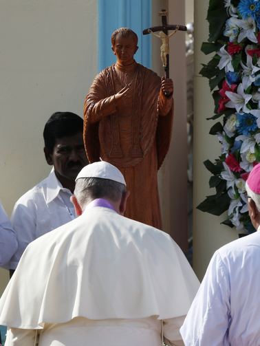 Pope Francis in front of stature of Joseph Vaz, a newly ordained saint, Jan 14 (CNS photo/Paul Haring).