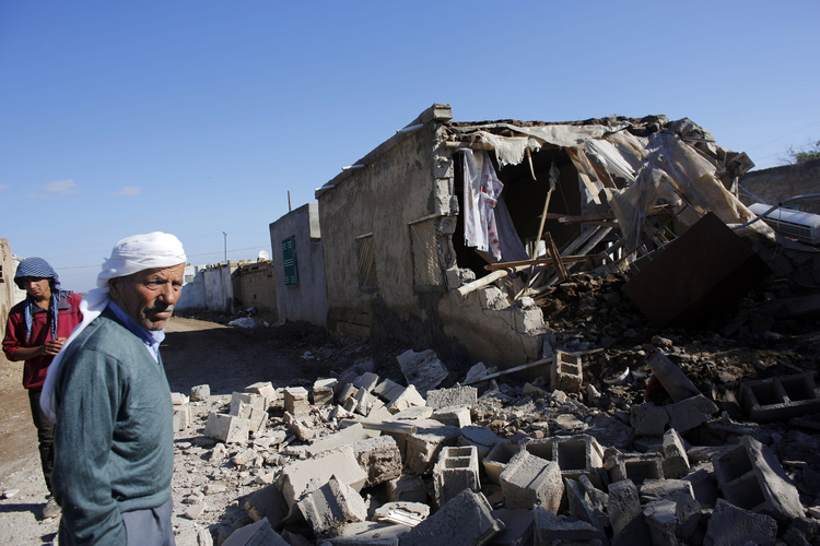 Local residents stand next to the debris of a house hit by a mortar shell from the Syrian side of the border in Alanyurt village near the Turkish-Syrian border Sept. 29. (CNS photo/Murad Sezer, Reuters)