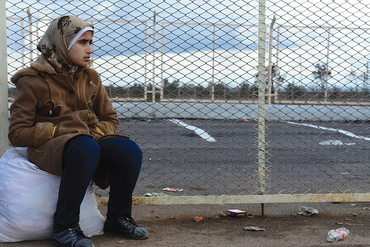 FAR FROM HOME. A Syrian girl in Turkey awaits a transport to a refugee camp.
